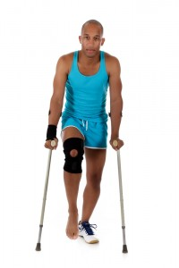 post surgery - young man with crutches and knee brace