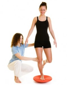 Girl on wobble cushion and physio