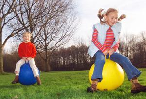 children-bouncing-on-balls